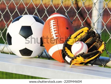 Sport balls. Soccer ball, american football and baseball in yellow glove. Outdoors