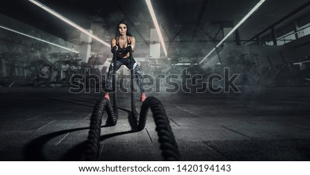 Sport. Battle ropes session. Attractive young fit sportswoman working out in functional training gym doing exercise with battle ropes.