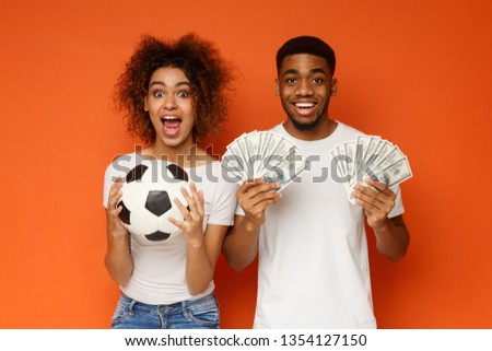 Sport bet excitement and family lifestyle. Excited african-american couple enjoying their win, standing with soccer ball and lots of money, orange background #1354127150
