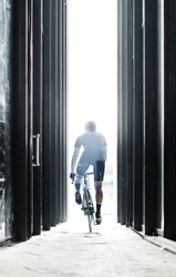 Sport bike man riding inside urban glass tunnel with light.