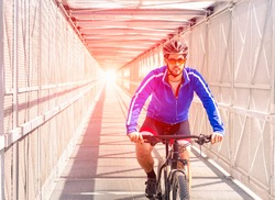 Sport bike man riding inside urban tunnel with light - Healthy cyclist on professional bicycle training day inside metal bridge - Concept of active green lifestyle and outdoor hobby - Sun halo filter