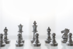Sport board game, Business and planning concept. Closeup of King, Queen, Bishop, knight and pawn silver chess pieces on glass table.