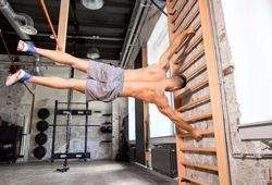sport, bodybuilding, fitness and people concept - young man exercising on gymnastics wall bars in gym