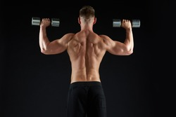 sport, bodybuilding, fitness and people concept - young man with dumbbells flexing muscles over black background from back