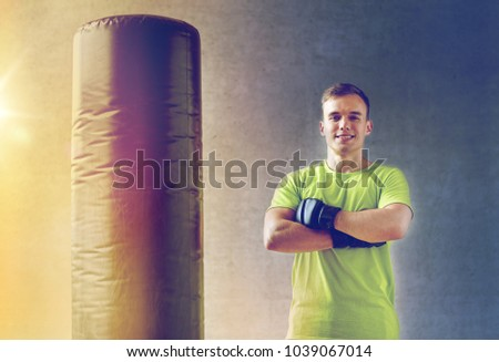 sport, box and people concept - young man with boxing gloves and punching  bag in 3f8e1b88c3