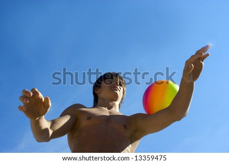 Sport build teenager boy with variegated ball against sky (series Sport, Extreme, Mountains, Horses and Teenagers)