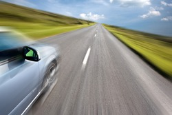 Sport car driving at high speed in empty road - motion blur