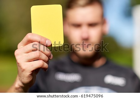sport, caution, game and people - referee on football field showing yellow card