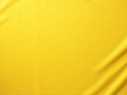 Sport Clothing Fabric Texture Background. Top View of Cloth Textile Surface. Yellow Football Shirt. Text Space