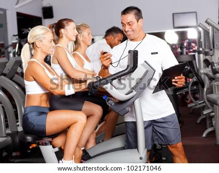 sport coach timing cyclist on gym bike