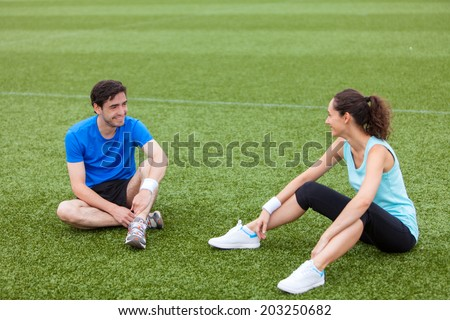 Sport coach training a young attractive woman on a stadium