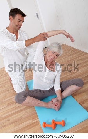 Sport coach training senior woman with stretching exercises