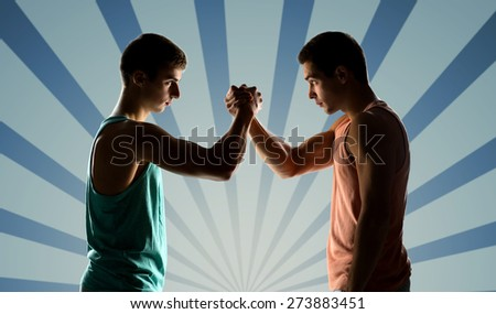 sport, competition, strength and people concept - two young men arm wrestling over blue burst rays background