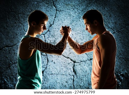 sport, competition, strength and people concept - two young men arm wrestling over concrete wall background
