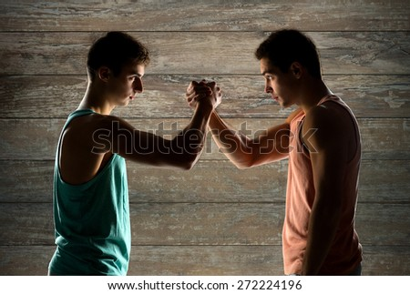 sport, competition, strength and people concept - two young men arm wrestling over wooden wall background
