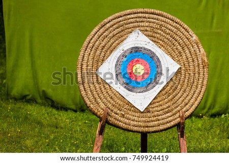 Sport competitions equipment concept. Shooting paper target and bullseye in haystack with many bullet holes #749924419