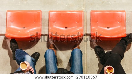 Sport competitions, recreation and relax. Row of plastic chairs and human legs in football stadium. Hot drink disposable cups with tea and coffee in hands.