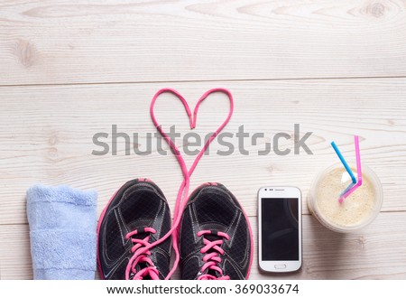 Sport concept, healthy lifestyle. Female sport shoes, towel, cell phone and smoothie in the cup on the floor, ready for jogging. Top view