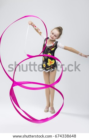 Sport Concepts. Little Happy Caucasian Female Rhythmic Gymnast In Professional Competitive Suit Doing Artistic Ribbon Spirals Exercises in Studio On White. Vertical Composition