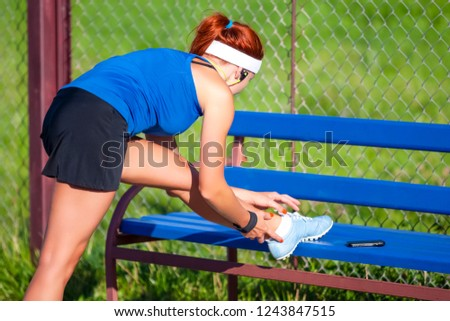 Sport Concepts. Sexy Caucasian Sportive Girl in Outdoor Outfit Having Legs Stretching Exercises Near Long Bench Outdoors While Listening to Music. Horizointal Image Composition