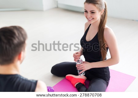 Sport connecting people friends relaxing after workout girl drinking water and man Side view of young couple in sports clothing sitting face to face and talking conversing