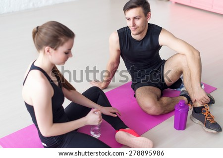 Sport connecting people friends relaxing after workout girl drinking water. Young couple in sports clothing sitting talking conversing