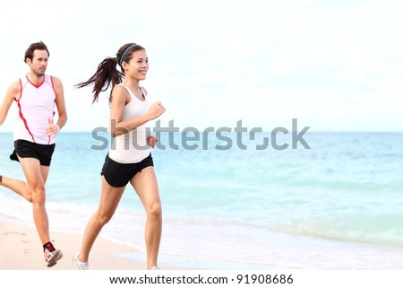sport - couple running on beach training for marathon run. Young multiracial couple runners, smiling asian female fitness model and caucasian male model.