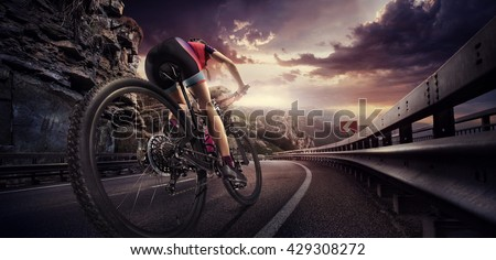 Sport. Cyclist riding a bike on an open road to the sunset