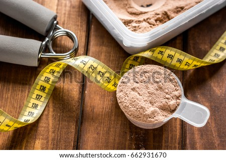 sport diet nutrition and fitness equipment , bars and measure tape wooden background
