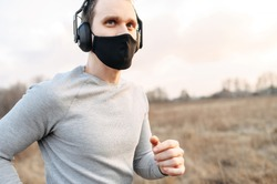 Sport during quarantine, self-isolation in the countryside. A young athletic guy is jogging on a dirt road in the meadow. He is wearing a black medical mask and headphones