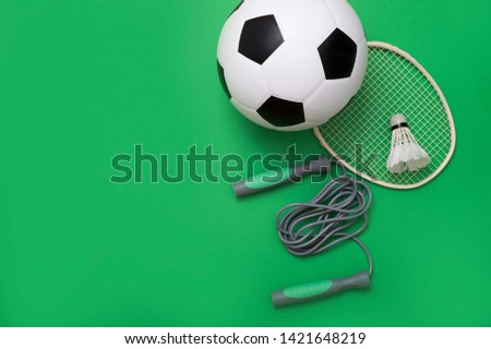 Sport equipment and ball on green background