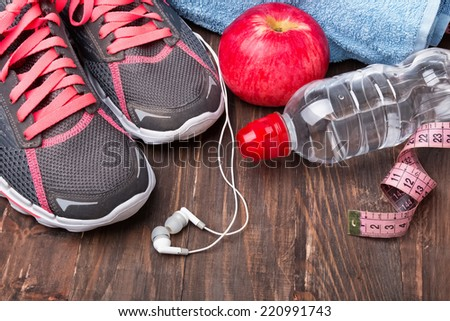 Sport equipment. Sneakers, water and earphones on wooden background #220991743