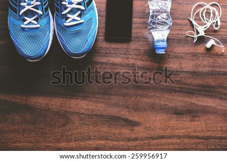Sport equipment. Sneakers, water, earphones and phone on wooden background. Focus is only on the sneakers.