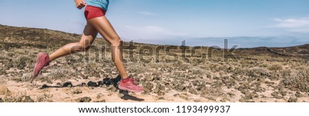 Sport exercise fitness female athlete runner running on trail run race in desert panorama banner. Closeup of legs and running shoes.