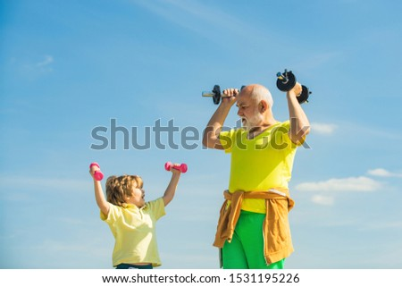 Sport exercise for kids. Boy is doing exercises to develop muscles. Grandfather helping kid exercising with dumbbells