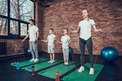 Sport Family With Jump Ropes In Fitness Club. Healthy Lifestyle. Training Exersises Repeat. Sunny Day. Gym Carpet. Work Out. White Shirt. Sunny Day. Active Occupation. Body Stamina.