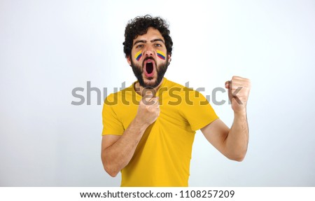 Sport fan screaming for the triumph of his team. Man with the flag of Colombia makeup on his face and yellow t-shirt.