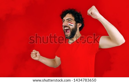 Sport fan screaming for the triumph of his team. Man with the flag of Egypt makeup on his face and red t-shirt and red background. #1434783650