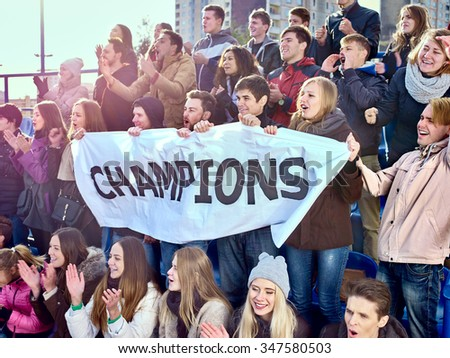 Sport fans holding very big champions banner  and singing on tribunes. Group people.