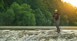 Sport fisherman hunting predator fish. Outdoor fishing in river during sunrise. Hunting and hobby sport.