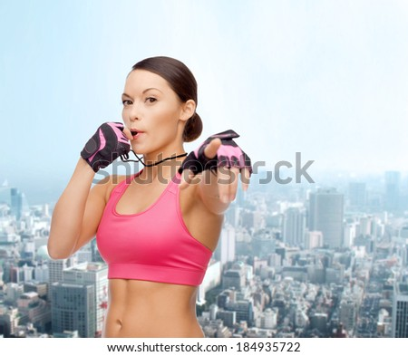 sport, fitness and healthcare concept - beautiful asian personal trainer with whistle