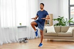 sport, fitness and healthy lifestyle concept - indian man running on spot at home