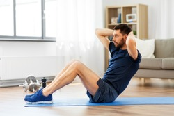 sport, fitness and healthy lifestyle concept - man making abdominal exercises at home