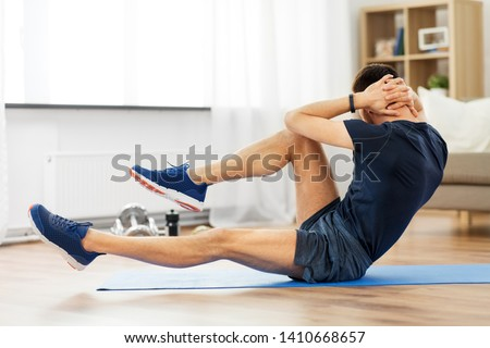 Photo of  sport, fitness and healthy lifestyle concept - man making bicycle crunch on exercise mat and flexing abs at home