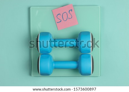 Sport, fitness concept. Losing weight. Floor scales with memo piece of paper with the word SOS and dumbbells on a blue background. Top view.