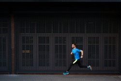 Sport, fitness concept. Sporty man in a blue shirt running outdoors, spring running, attractive Caucasian runner jogs fast over urban gray background