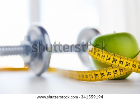 sport, fitness, diet and objects concept - close up of dumbbell and green apple with measuring tape