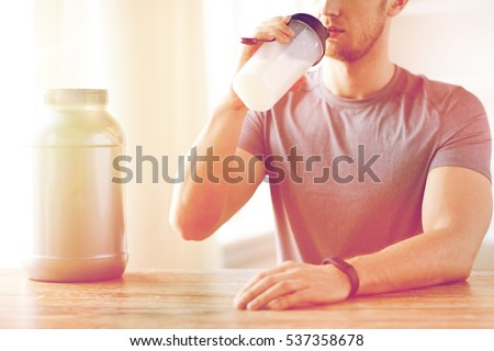 Shutterstock sport, fitness, healthy lifestyle and people concept - close up of man in fitness bracelet with jar and bottle drinking protein shake