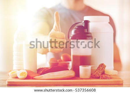 sport, fitness, healthy lifestyle, diet and people concept - close up of man with food rich in protein showing thumbs up #537356608