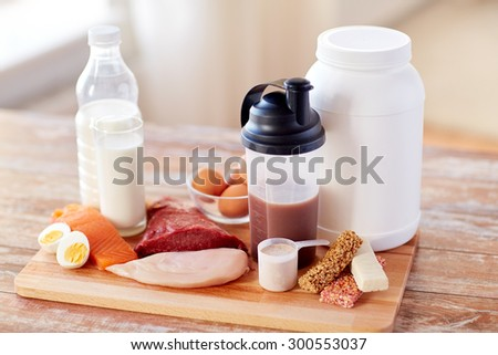 sport, fitness, healthy lifestyle, diet and people concept - close up of natural protein food and additive on wooden table